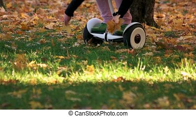 Riding gyroscooter on the grass. Close up. Picking up fallen...