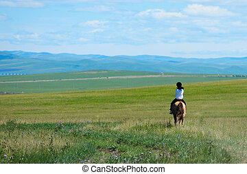 Riding horse in grassland of Hulun Buir League of...