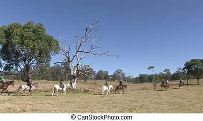 Riding horses on a ranch - A wide shot of people in...