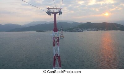 Riding in the cabin of Vinpearl cable car over the Nha Trang bay in Vietnam. Camera moves away from tower