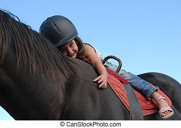 riding little girl - very young little girl on her black ...