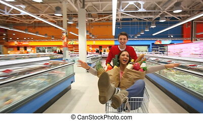 Riding market cart - Cheerful couple having fun in...