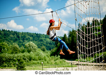 Riding on a zip line - Young woman in casual wearing with ...