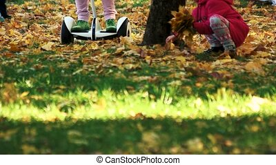 Riding on the grass covered with fallen leaves.