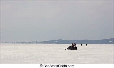 Riding snowmobile on winter lake