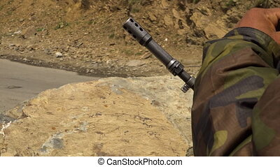 Rifle barrel in guard's hands near dirt road - Close up of a...