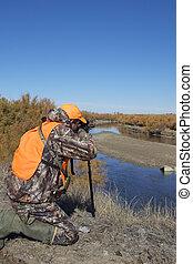 a rifle deer hunter along the arkansas river in fall