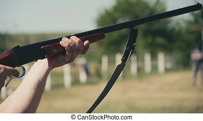 Rifleman keeping a rifle, raising it and shooting on a range...