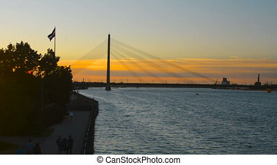 Riga Old Town riverside panorama with cable bridge silhouette in evening sunset
