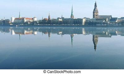 Riga Old Town Skyline seen over foggy river Daugava