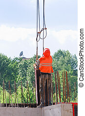 Rigger builder worker operating with straps