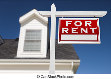 Right Facing For Rent Real Estate Sign In Front of House and Deep Blue Sky.