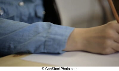 Right hand in denim shirt draws sketch on sheet of paper