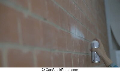 Right hand of man painting on brick wall with spray indoors....