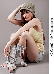 Right pose of a fashion model sitting with cap and woolen leggings on the floor indoor studio