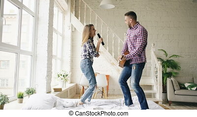 rigolote, femme, amusement, leur, danse, couple, guitar., lit, aimer, tv, contrôleur, avoir, pendant, homme, maison, vacances, chant, jouer, heureux