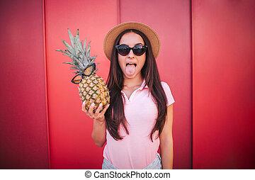 rigolote, femme, lunettes soleil, stands, elle, tient, isolé, glasses., tongue., arrière-plan., elle, appareil-photo., ananas, girl, poses, rayé, rouges, spectacles