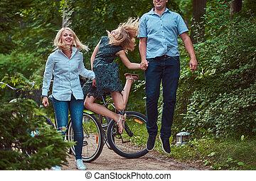 rijden, fiets, gezin, geklede, springt, aantrekkelijk, hebben vermaak, kleren, ongedwongen, park.