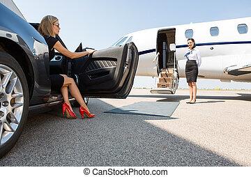 rijke vrouw, aan het benen, van, auto, op, terminal