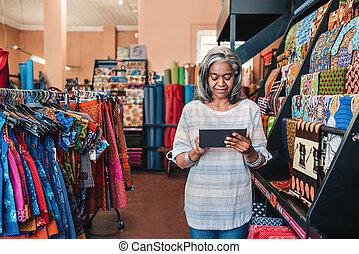 rijp vrouw, gebruik, een, digitaal tablet, in, haar, textielproducten, winkel