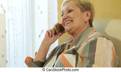 rijp vrouw, kletsende, op de telefoon