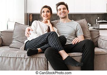 rilassante, coppia, giovane, divano, ritratto, sorridente