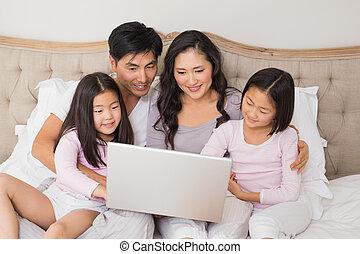rilassato, famiglia quattro, usando computer portatile, letto