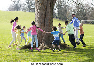 Ring -A -Rosie - A group of children with two adults holding...