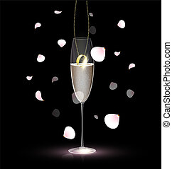 against a background of rose petals is a gold ring on a chain inside a glass of champagne