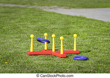 Ring throw summer game on a green lawn