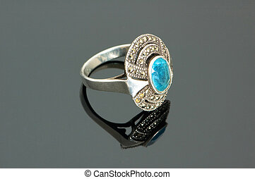 Ring with blue stone on the reflective background