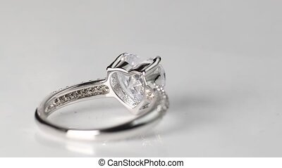 Ring with large heart shaped diamond rotating on gray...