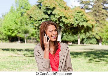 ringa, henne, lysande, medan, talande, till, se, grässlätt, le womanen, område, omkring