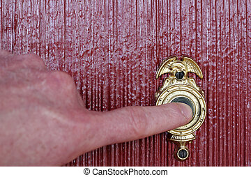 Ringing Doorbell - Finger of a mans hand ringing a gold and...