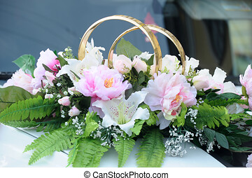 Rings and flowers on the wedding car
