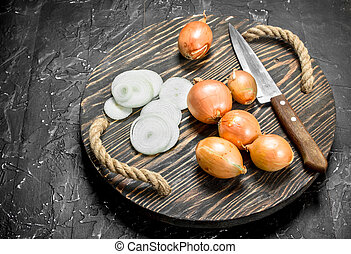 Rings and heads of onions on tray with a knife.