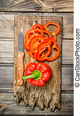 Rings of fresh pepper and one red pepper on a cutting Board with a knife.