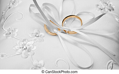 rings on a pillow - two gold wedding rings on a pillow