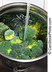 Rinsing raw broccoli under a tap. - Rinsing broccoli in a...