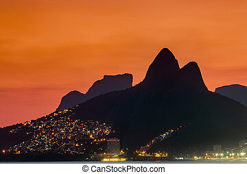 Two Brothers Mountain and Pedra da Gavea, Vidigal Favela Lights at Sunset in Rio de Janeiro, Brazil.
