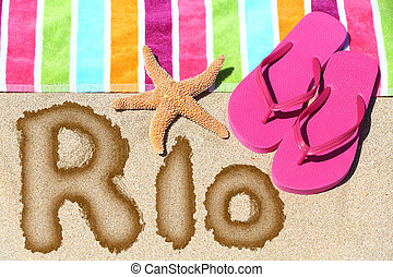 Rio written on beach sand with a colorful towel