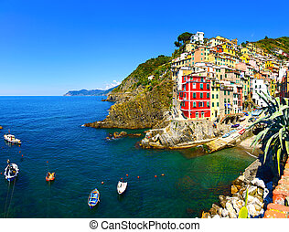 Riomaggiore village, rocks, boats and sea at sunset. Cinque...