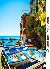 Riomaggiore village street, boats and sea. Cinque Terre,...