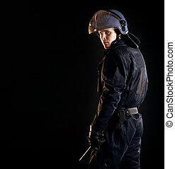 Riot Police Officer in the Dark - Portrait of a serious riot...