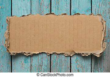 Rip cardboard piece on blue vintage wood background