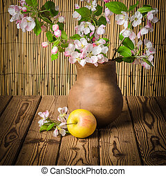 Ripe apple and blossoming branch of an apple-tree in a clay jar, close-up