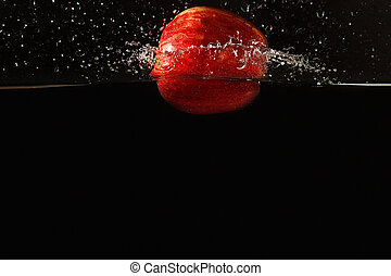 Ripe apple falling into the water with a splash on a dark background closeup
