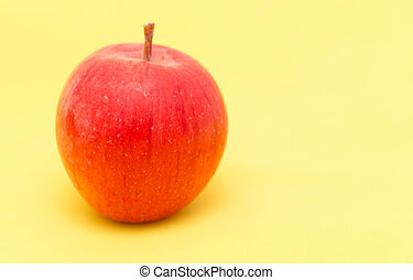 ripe apple on a yellow background