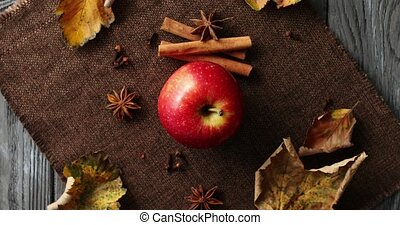 Ripe apple with fallen leaves and spices - Top view of...
