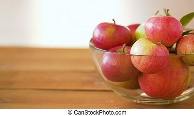 ripe apples in glass bowl on wooden table - fruits, food and...